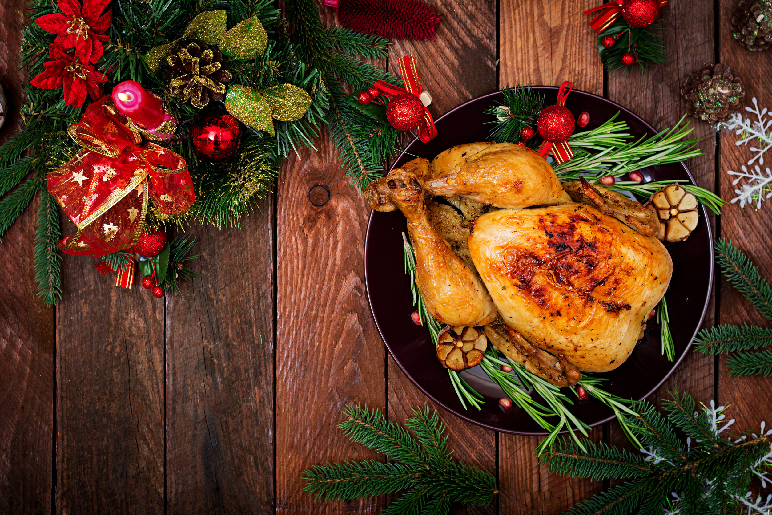 Roast turkey garnished and presented on wooden top with festive garland